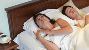 Man snoring with mouth closed next to tired woman