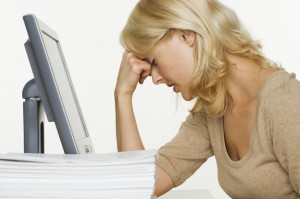 Frustrated Woman at Computer With Stack of Paper.  Many people could be suffering from central sleep apnea.
